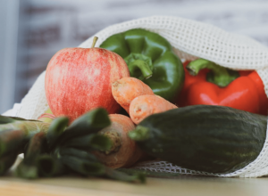 A bag of plastic free vegetables lay on the countertop. Green pepper, apple and more